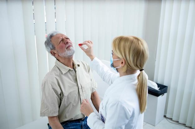 Медицинский работник берет образец на анализ у пожилого человека для проверки на возможную коронавирусную инфекцию.
