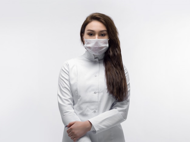 Medical worker in white doctor uniform and white protective mask