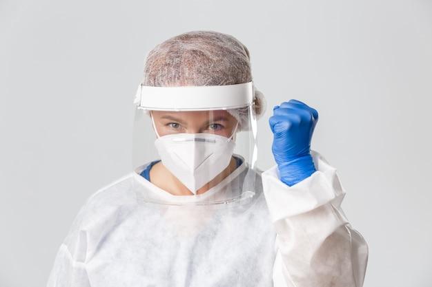 医療従事者、covid-19パンデミック、コロナウイルスの概念。個人用保護具を身に着けた自信と希望に満ちた女性医師のクローズアップは、勝利を支持し、支持し、喜んで拳を握り締めます。