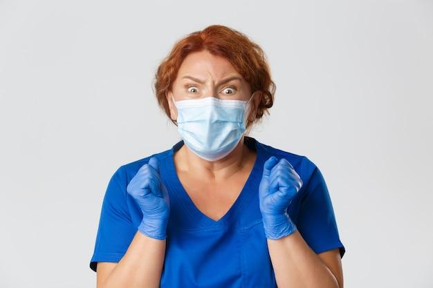 医療従事者、covid-19パンデミック、コロナウイルスの概念。怖がっている女性医師、フェイスマスクと手袋の看護師のクローズアップ恐怖から揺れ、カメラ、灰色の背景に恐怖を探しています。