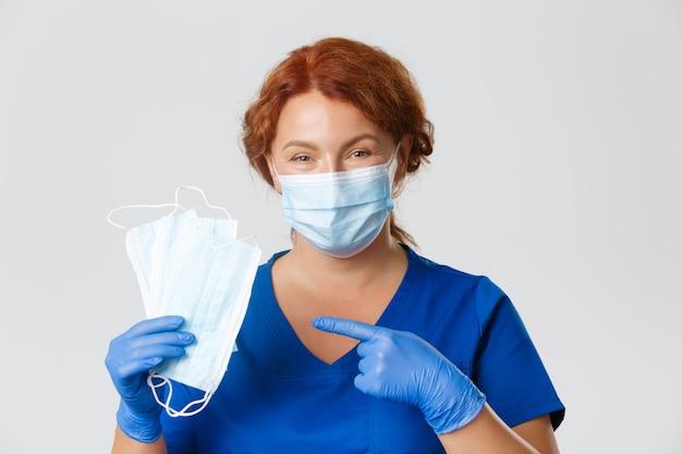 医療従事者、covid-19パンデミック、コロナウイルスの概念。笑顔の思いやりのある女性看護師、フェイスマスクを指しているゴム手袋の医師のクローズアップ、社会的距離を尋ね、主な推奨事項を説明します。
