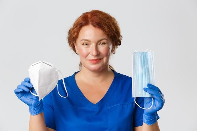 医療従事者、covid-19パンデミック、コロナウイルスの概念。笑顔の女性医師のクローズアップ、医師は保護具をお勧めします、フェイスマスクと呼吸器、灰色の背景を示しています。
