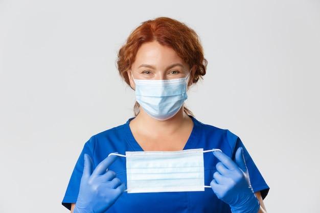 医療従事者、covid-19パンデミック、コロナウイルスの概念。笑顔の優しい女性医師のクローズアップ、医師はゴム手袋でそれを保持し、フェイスマスクを着用する方法を説明します。