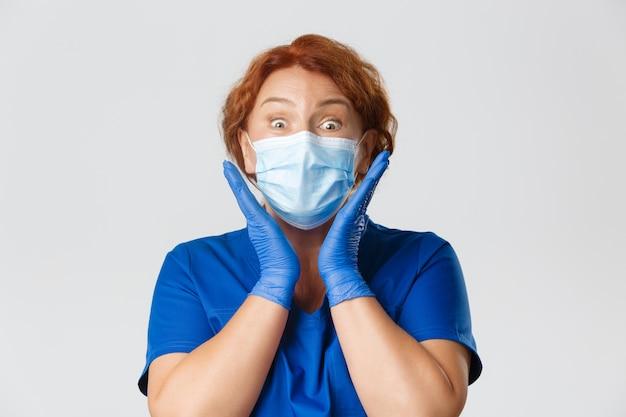 医療従事者、covid-19パンデミック、コロナウイルスの概念。驚いて感動した中年女性看護師、フェイスマスクとゴム手袋をはめた医師のクローズアップ。