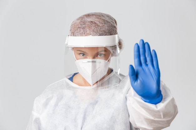 Medical workers, covid-19 pandemic, coronavirus concept. close-up of serious-looking concerned female doctor in personal protective equipment, face shield and respirator show stop gesture, warning.