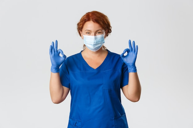 Medical workers, covid-19 pandemic, coronavirus concept. confident smiling redhead doctor, female nurse in medical mask, gloves, showing okay gesture, provide safe checkup during virus outbreak.
