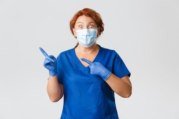 Медицинские работники, пандемия covid-19, концепция коронавируса. взволнованная и удивленная, счастливая женщина-врач, врач в маске и перчатках объявляет о чем-то великом, указывая пальцами в верхнем левом углу.