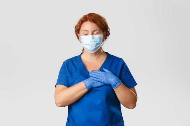 의료진, covid-19 대유행, 코로나 바이러스 개념. 행복하고 꿈꾸는 빨간 머리 여성 간호사, 안면 마스크와 장갑의 중년 의사는 눈을 감고 손을 심장에 대고 공상하며 명심하십시오.