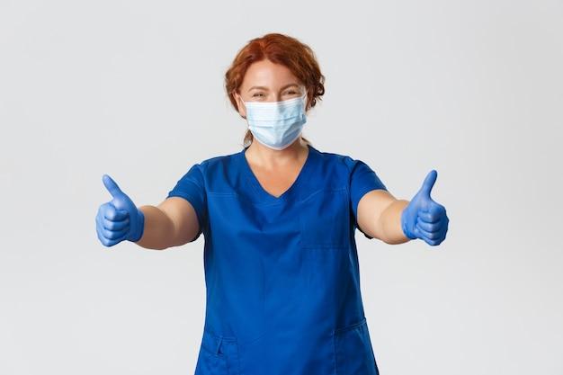 Медицинские работники, пандемия covid-19, концепция коронавируса. счастливая улыбающаяся женщина-врач, медсестра средних лет в медицинской маске и перчатках показывает палец вверх, гарантирует качественное обслуживание в клинике.