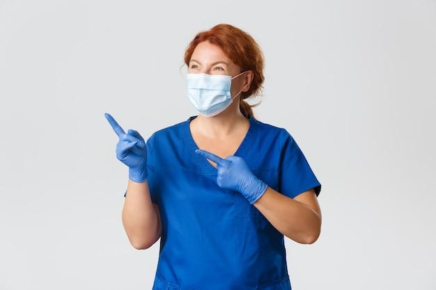 Медицинские работники, пандемия covid-19, концепция коронавируса. портрет счастливой улыбающейся женщины-врача в лицевой маске, резиновых перчатках и скрабах, восторженно улыбаясь и указывая в левый верхний угол.