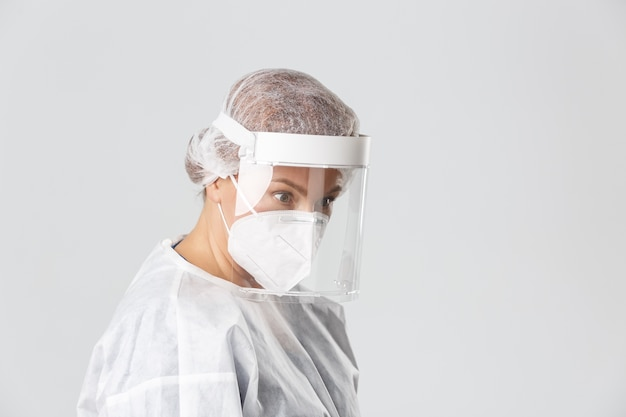 Medical workers, covid-19 pandemic, coronavirus concept. profile of surprised female doctor in personal protective equipment looking right lower angle at patient, standing grey background.
