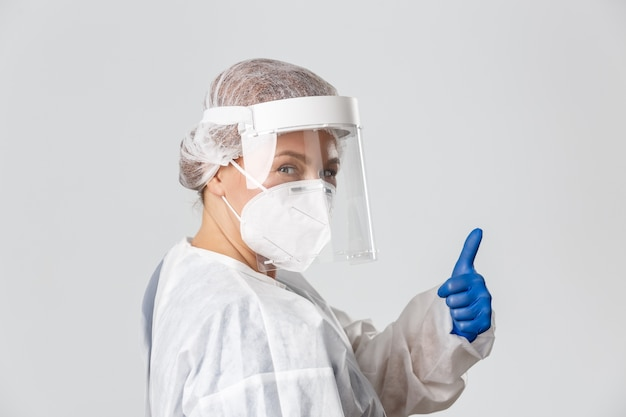 Medical workers, covid-19 pandemic, coronavirus concept. sassy professional female doctor in personal protective equipment, assure people all under control, showing thumbs-up and smiling.