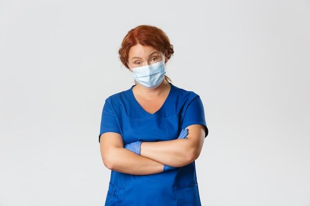 Медицинские работники, пандемия covid-19, концепция коронавируса. скептически и осуждающе, серьезного вида женщина-врач, врач скрещивает руки и скептически поднимает брови, надевает маску и перчатки.