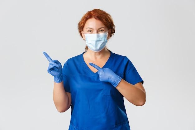 Медицинские работники, пандемия covid-19, концепция коронавируса. улыбается счастливая женщина-врач, женщина-медсестра в маске для лица, резиновые перчатки и скрабы, указывая пальцами влево, показывая аквертификацию, серый фон.