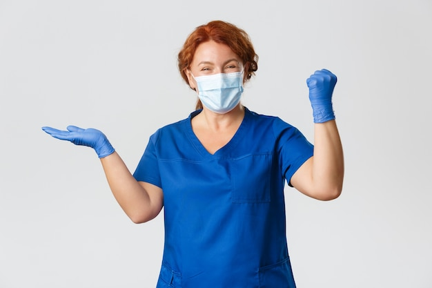 Медицинские работники, пандемия covid-19, концепция коронавируса. успешная и довольная, счастливая женщина-врач, медсестра в маске и перчатках, что-то держит в руках и торжествует, веселый кулачковый насос.