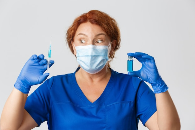 医療従事者、パンデミック、コロナウイルスの概念。フェイスマスクと手袋をはめた驚きの興奮した女性医師が、ついにウイルスからのワクチンを手に入れ、興奮した表情のアンプルと注射器を手にしました。