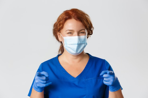Medical workers,  pandemic, coronavirus concept. close-up happy female doctor, physician or nurse in scrubs, face mask and gloves smiling friendly