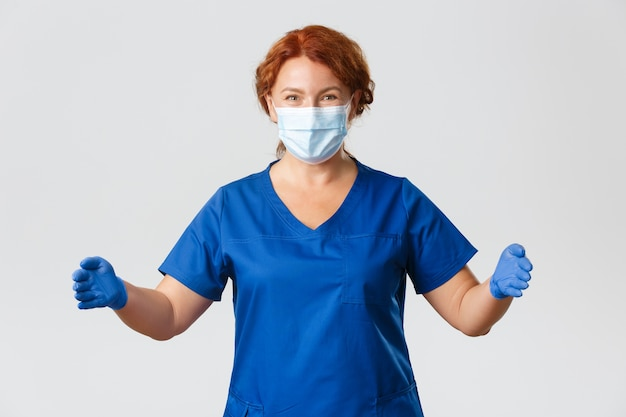 医療従事者、パンデミック、コロナウイルスの概念。幸せな笑顔と驚きの女性医師、スクラブとフェイスマスクの看護師は、大きなものを持っているかのように手を広げ、大きなサイズを見せます。