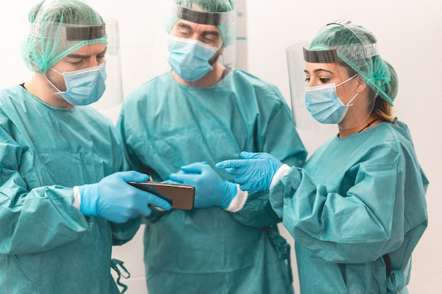 Medical workers using mobile phone inside hospital corridor during coronavirus outbreak
