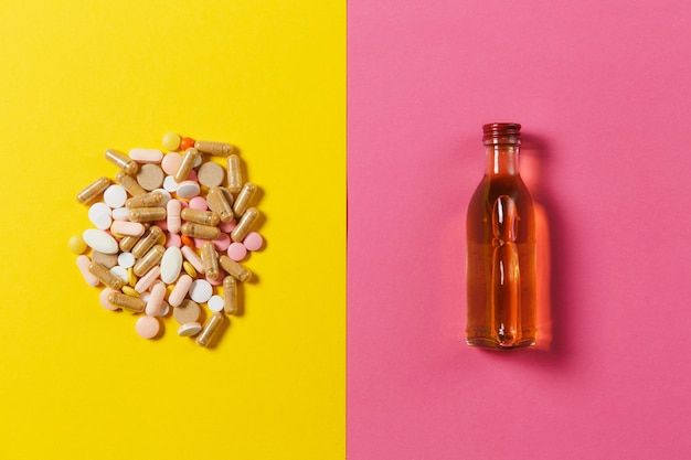 Medication colorful round tablets arranged abstract, bottle alcohol on yellow pink background