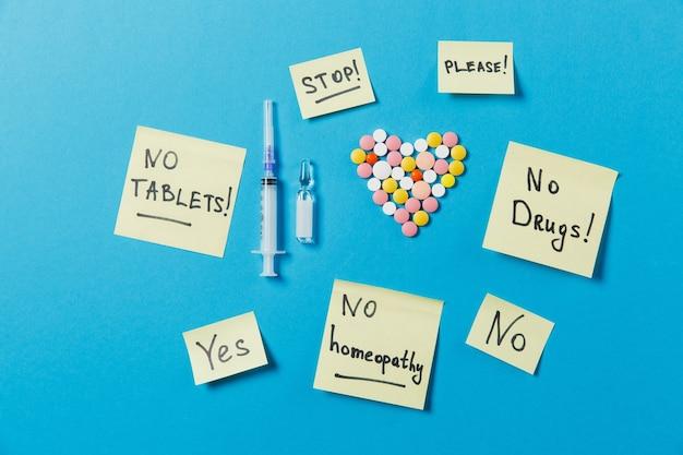 Compresse rotonde colorate di farmaci a forma di cuore isolato su sfondo blu