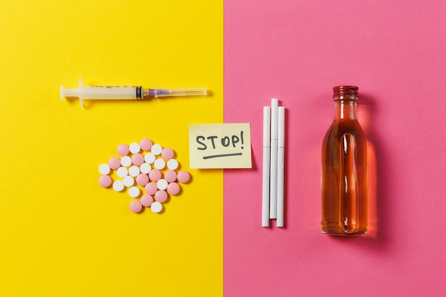 Medication colorful round tablets pills arranged abstract, empty syringe needle bottle alcohol, cigarettes on yellow pink rose background. paper sticker sheet text word stop. choice healthy lifestyle.