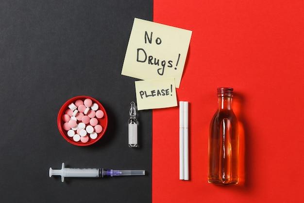 Pillole di compresse rotonde colorate di farmaci aghi di siringa vuoti, sigarette di fiale di alcol in bottiglia