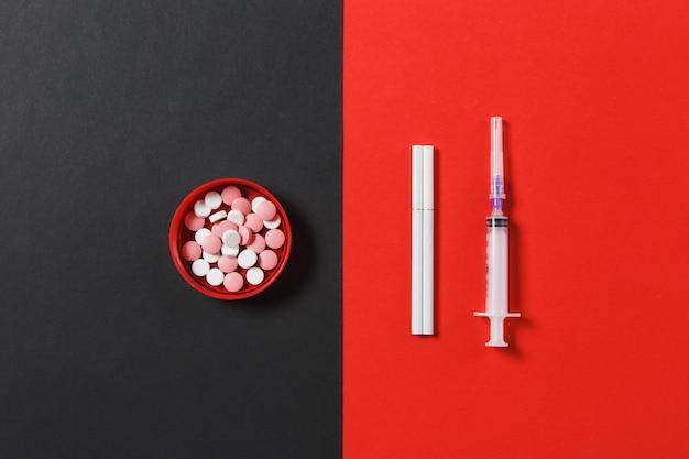 Medication colorful round tablets pills, empty syringe needle, cigarettes