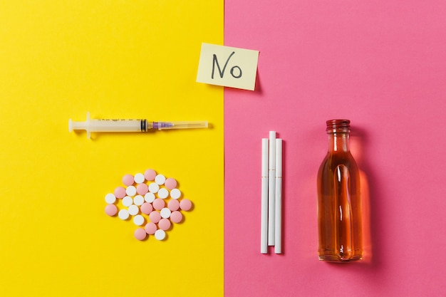 Farmaci compresse colorate pillole astratte, ago vuoto della siringa, alcool in bottiglia, sigarette su sfondo rosa rosa gialla