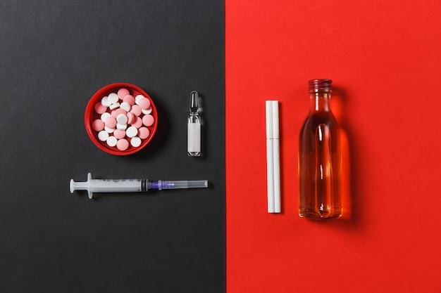 Pillole variopinte delle compresse del farmaco astratte, ago vuoto della siringa, bottiglia con il cognac dell'alcool, whisky, fiala, sigarette