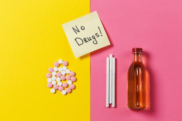 Pillole di compresse colorate di farmaci disposte in astratto, bottiglia di alcol, sigarette su sfondo rosa rosa gialla