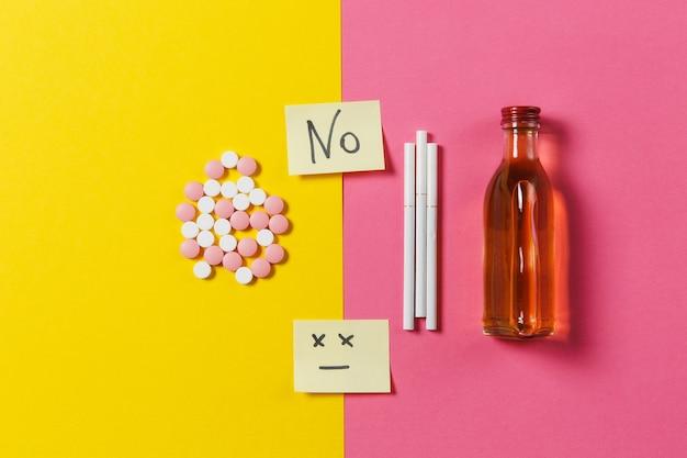 Pillole di compresse colorate di farmaci disposte in astratto, alcool in bottiglia, sigarette su sfondo di colore rosa rosa gialla