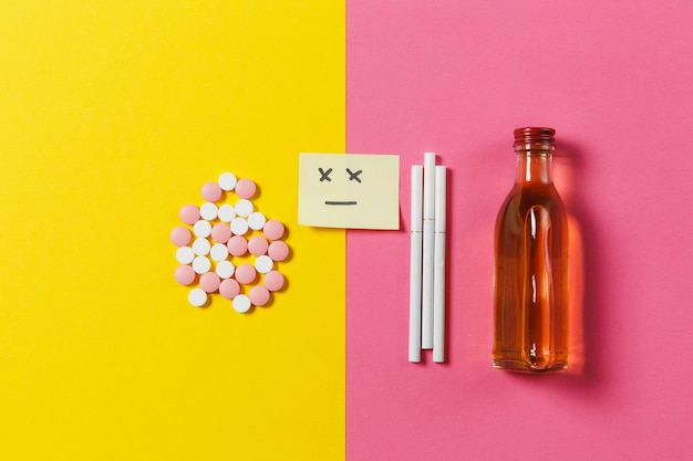 Medication colorful tablets pills arranged abstract, bottle alcohol, cigarettes on yellow pink rose color background