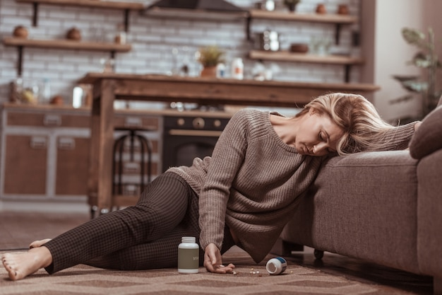 Medication poisoning. mature blonde-haired woman falling on floor near sofa after medication poisoning