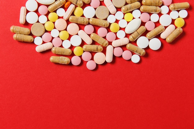 Лекарство белые красочные круглые таблетки расположены абстрактно на фоне красного цвета