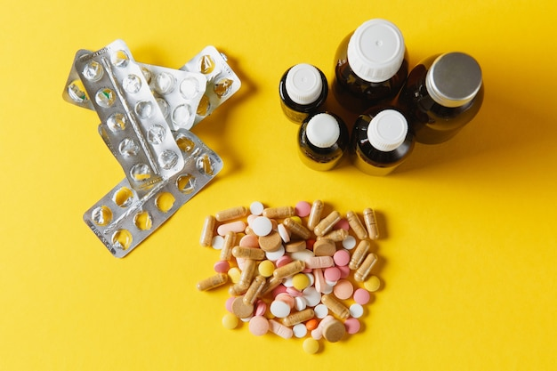Лекарства белые красочные круглые таблетки расположены абстрактно на фоне желтого цвета. таблетки упаковки флаконов для дизайна. концепция здорового образа жизни выбор лечения. скопируйте космическую рекламу.
