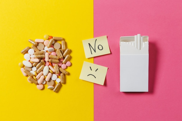 Medication white colorful round tablets arranged abstract pack of cigarettes on yellow color background. paper sticker sheet text word no sad slile face. choice healthy lifestyle concept. copy space.