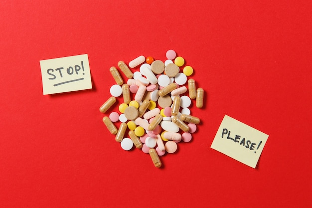 Medication white colorful round tablets arranged abstract on red color background