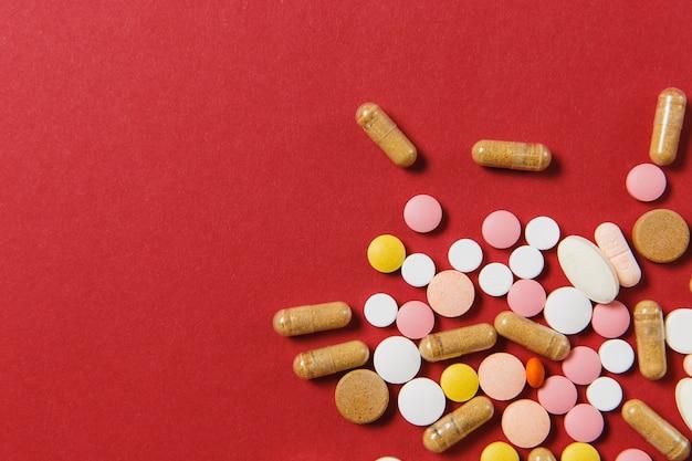 Compresse rotonde colorate bianche di farmaci disposte in astratto su sfondo di colore rosso Foto Gratuite