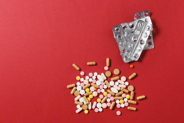 Compresse rotonde colorate bianche di farmaci disposte in astratto su sfondo di colore rosso
