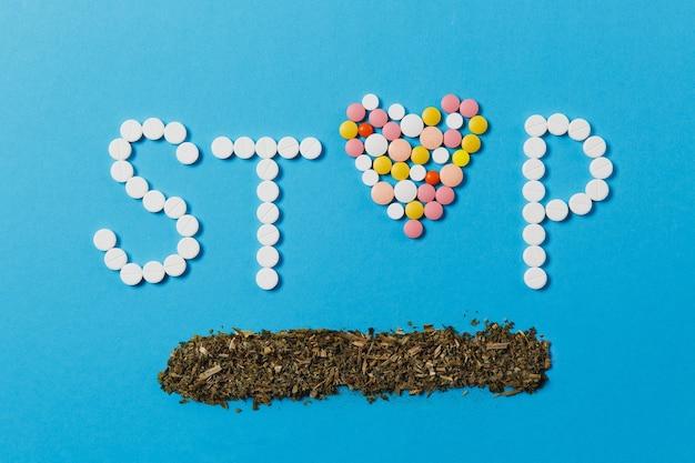 Лекарство белые, красочные круглые таблетки в слове stop, изолированные на синем фоне