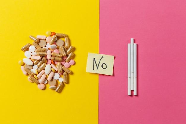 Pillole di compresse rotonde colorate bianche di farmaci disposte astratte tre sigarette su sfondo di colore giallo