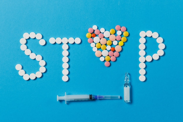 Medication white, colorful round tablets in word stop isolated on blue background