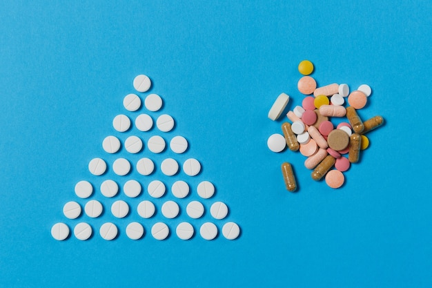 Белые круглые таблетки лекарства расположены в форме треугольника, изолированного на синем фоне. букет из разноцветных таблеток, геометрическая форма пирамиды. концепция здоровья, лечения, выбора, здорового образа жизни.