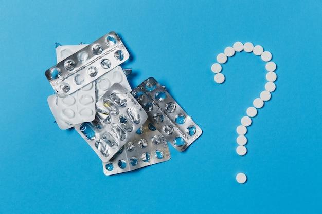 Белые круглые таблетки лекарства, расположенные в форме вопросительного знака, изолированного на синем цветном фоне