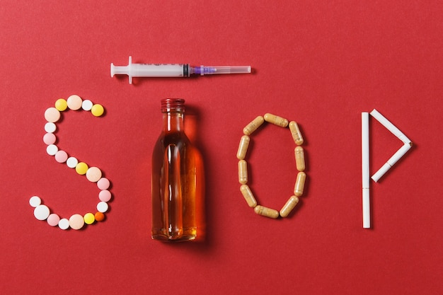 Medication white round tablets in word stop. creative composition with message stop drinking bottle alcohol empty syringe needle on black background. concept of choice, healthy lifestyle.