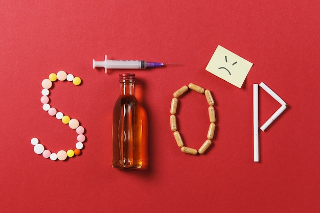 Compresse rotonde bianche del farmaco nella parola stop