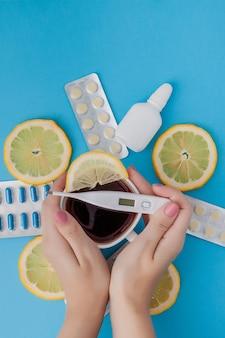 Лекарства, таблетки, градусник, народная медицина для лечения простуды, гриппа, тепла на синем фоне.