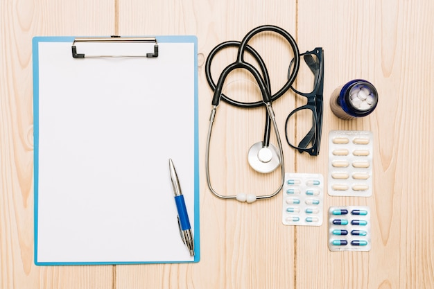 Medications and stethoscope near clipboard and glasses