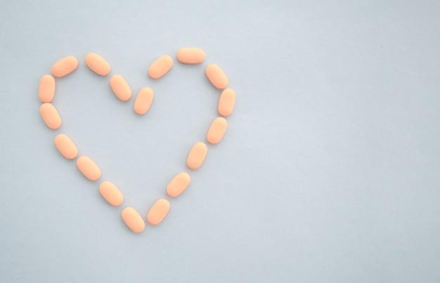 약물 정제는 파란색 배경에 하트 모양으로 배치됩니다. 심장병 치료의 개념